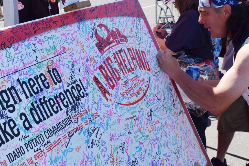 Man In Bandana With Big Helping Signature Board